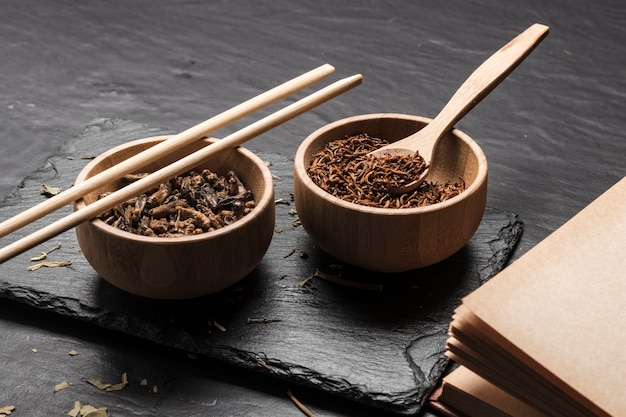 Wooden bowls with insects on slate board