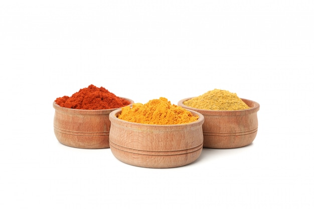 Wooden bowls with red pepper, curry and turmeric powder isolated on white
