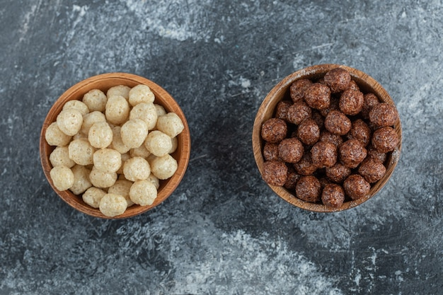 Wooden bowls with sweet corn balls on gray.