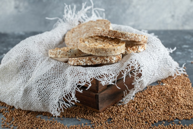 Wooden box of airy crispbread and raw buckwheat on marble surface