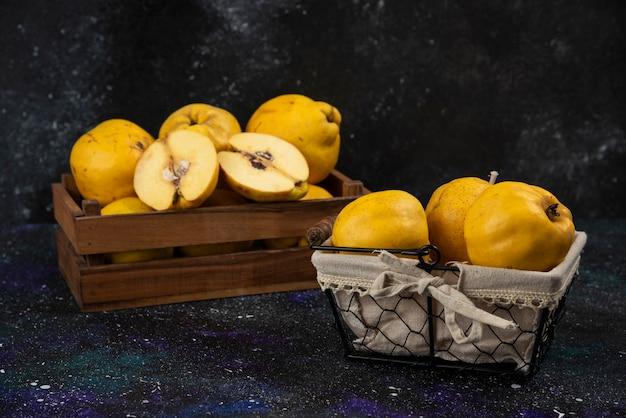 Scatola di legno e cesto di mele cotogne fresche mature sul tavolo scuro.