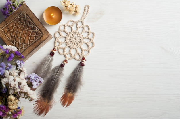 Wooden box and beige dream catcher, lit candle