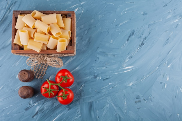 A wooden box of dry raw pasta with fresh red tomatoes on a marble table .