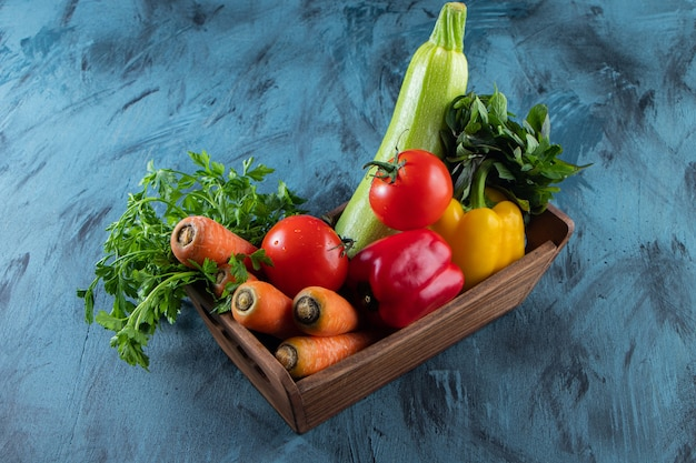 Wooden box of fresh fresh vegetables on blue surface.