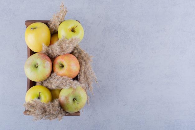 Scatola di legno di mele verdi fresche su pietra.