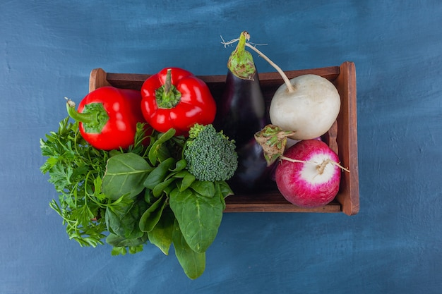 Wooden box of fresh healthy vegetables and greens on blue surface.