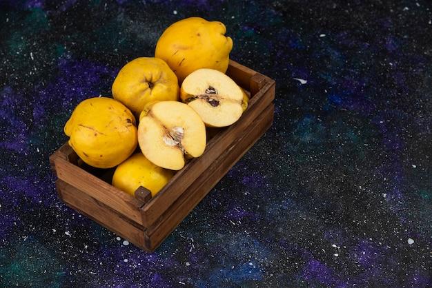 Scatola di legno di mele cotogne fresche mature sul tavolo scuro.