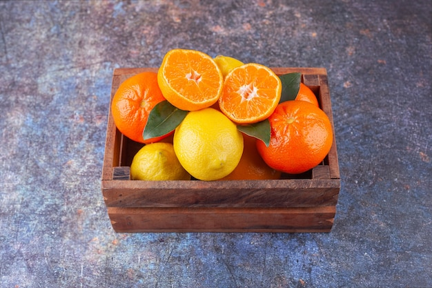 Wooden box full of fresh fruits on marble background.