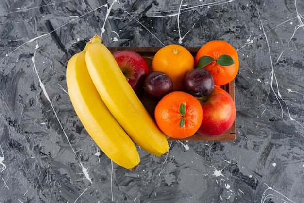 Wooden box full of fresh fruits on marble surface. Free Photo