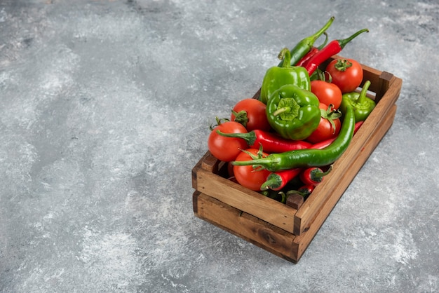 Wooden box full of fresh vegetables on marble.