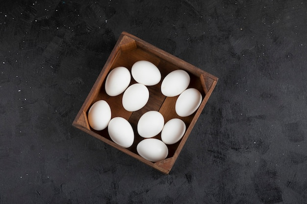 Wooden box full of organic raw eggs on black surface.