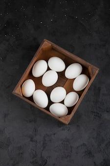 Scatola di legno piena di uova crude organiche sulla superficie nera.
