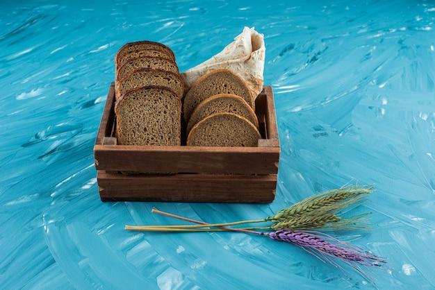 Una scatola di legno piena di pane fresco marrone a fette con spighe di grano su sfondo blu.