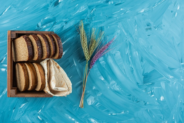 A wooden box full of sliced brown fresh bread with wheat ears on blue background .