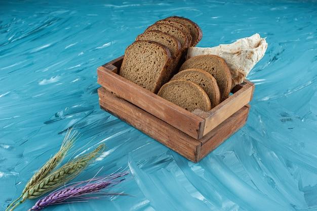 Una scatola di legno piena di pane fresco marrone affettato con spighe di grano sulla superficie blu