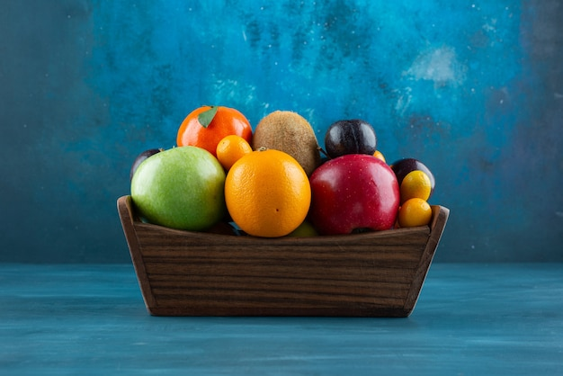 Wooden box full of various organic fruits on blue surface.