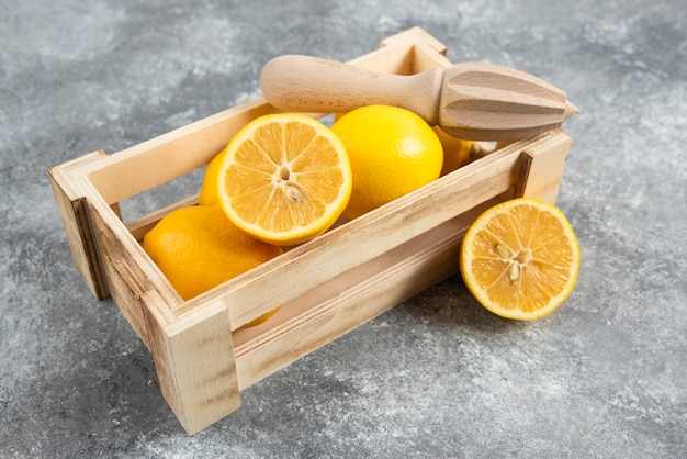 레몬 압착기와 함께 신선한 레몬으로 가득 찬 나무 상자.