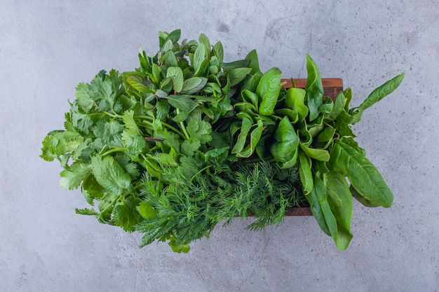 Wooden box of healthy fresh greens on blue.