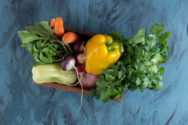 Wooden box of healthy fresh vegetables on blue surface.