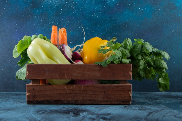 Wooden box of healthy fresh vegetables on blue wall.