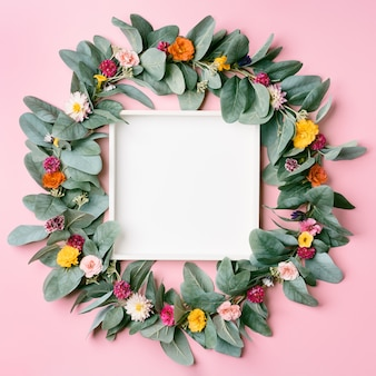 Wooden box inside a round floral frame of assorted flowers on a pink pastel background