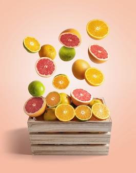 さまざまなオレンジとみかんが飛んでいる木箱、新鮮な柑橘系の果物