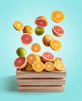 さまざまなオレンジとみかんが飛んでいる木製の箱、コピースペースで青い背景から分離