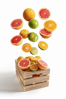 白い背景から隔離の飛行オレンジとみかんの詰め合わせの木箱