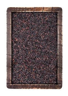 Деревянная коробка сырцового органического черного риса венеры на белой предпосылке. взгляд сверху