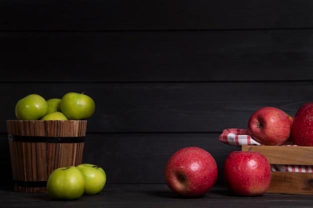 빨간 사과와 어두운 배경에 녹색 사과 나무 상자. 고품질 사진