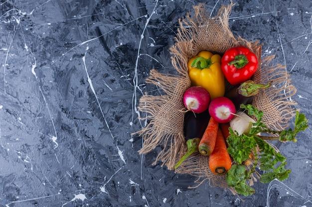 Деревянная коробка спелых здоровых овощей и зелени на синем фоне.