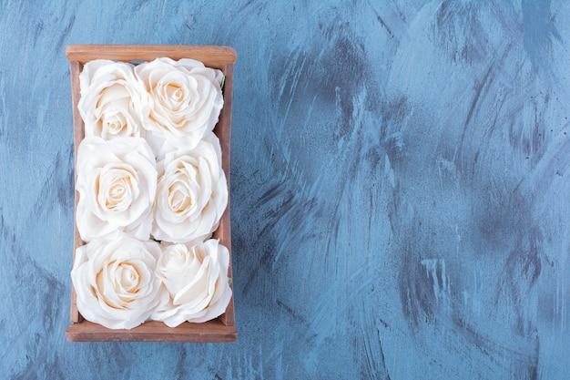 青に白いバラの花の木箱。