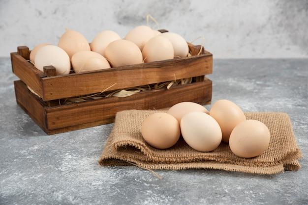 Scatola di legno di uova crude organiche sulla superficie di marmo.