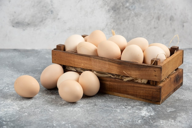 Wooden box of organic raw eggs on marble surface.