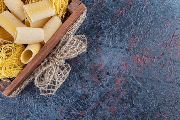 Una scatola di legno di spaghetti crudi con pomodori rossi freschi e aglio su uno sfondo scuro.