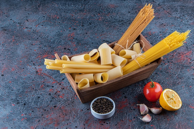 Una scatola di legno di pasta cruda con pomodori rossi freschi e aglio su uno sfondo scuro.