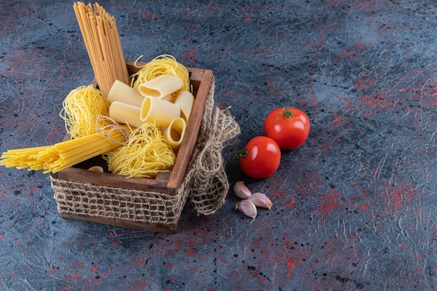 Una scatola di legno di pasta cruda con pomodori rossi freschi e aglio su una superficie scura.