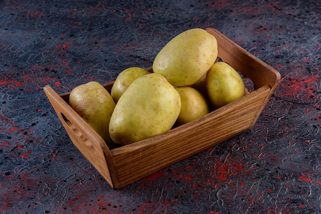 A wooden box of raw potatoes food on a dark background.
