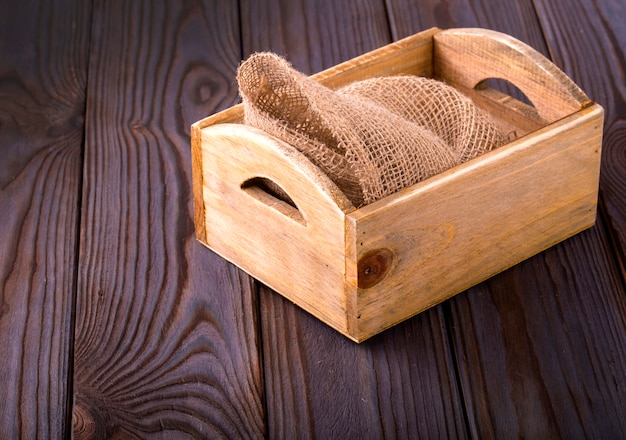 Wooden box on sack cloth on wooden background