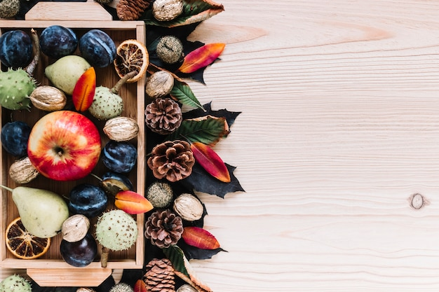 Wooden box with assortment of autumn fruits