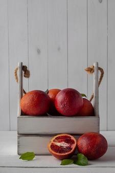 白いテーブルに血まみれのオレンジが入った木箱、コピースペース。ジューシーな柑橘系の果物