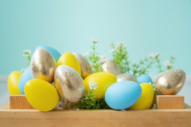 파란색 벽에 파란색, 노란색, 금색 부활절 달걀과 나무 상자