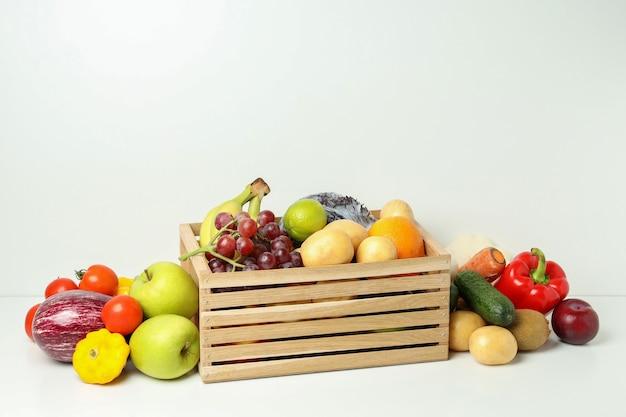 Деревянная коробка с разными овощами и фруктами на белом столе