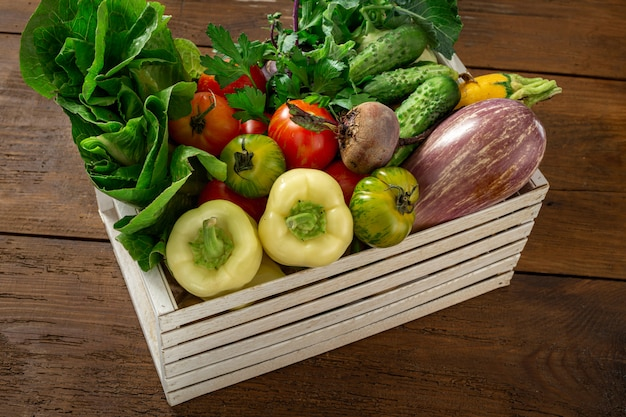 Wooden box with different vegetables harvesting