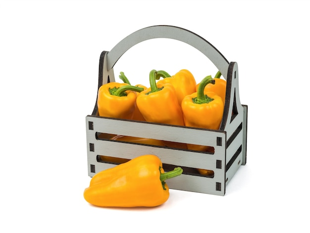 Wooden box with fresh bell pepper isolated on a white background. vegetarian food.