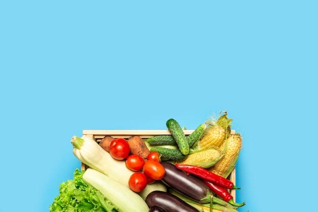 青色の背景に新鮮な野菜と木製の箱。