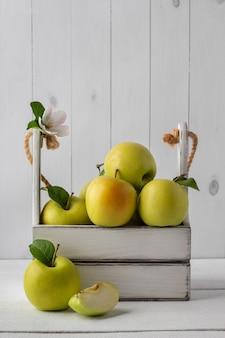 Деревянная коробка с органическими зелеными яблоками на белом столе, копией пространства. вкусные сезонные фрукты
