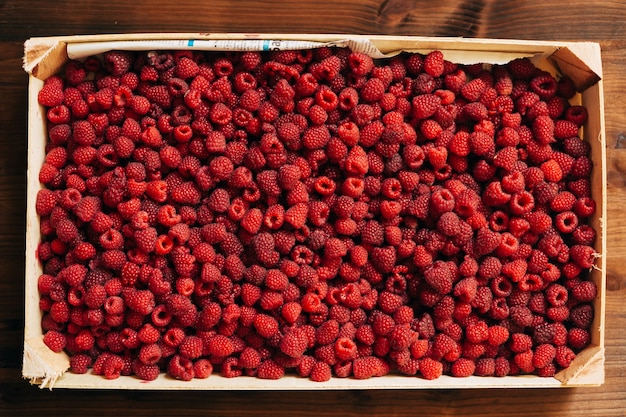 A wooden box with ripe raspberry berries the texture and background of a large amount of raspberries