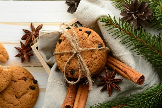 계피 스틱과 침엽수 향기로운 가지로 구성된 달콤한 초콜릿 칩 쿠키가 들어있는 나무 상자.