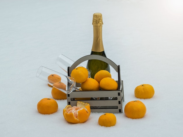 Wooden box with tangerines, glasses and a bottle of champagne in the snow.